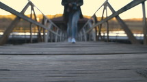 a woman with a camera walking on a wood dock