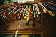 Multi-colored rosary beads hanging on a rod outdoors.