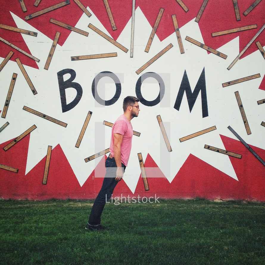 Man falling forward in front of a sign with the words BOOM