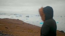 a woman looking out at icebergs