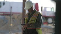 man texting on a construction site