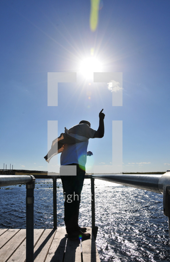 man standing at the edge of a dock with his finger pointing up