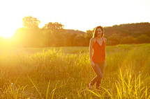 Woman in grass field at sunset