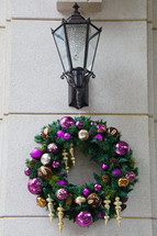 Purple and gold ornaments on pine wreath hanging under coach lamp on stone wall.