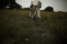 Joseph walking through a field