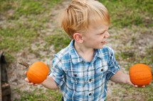 Boy holding two pumpkins
