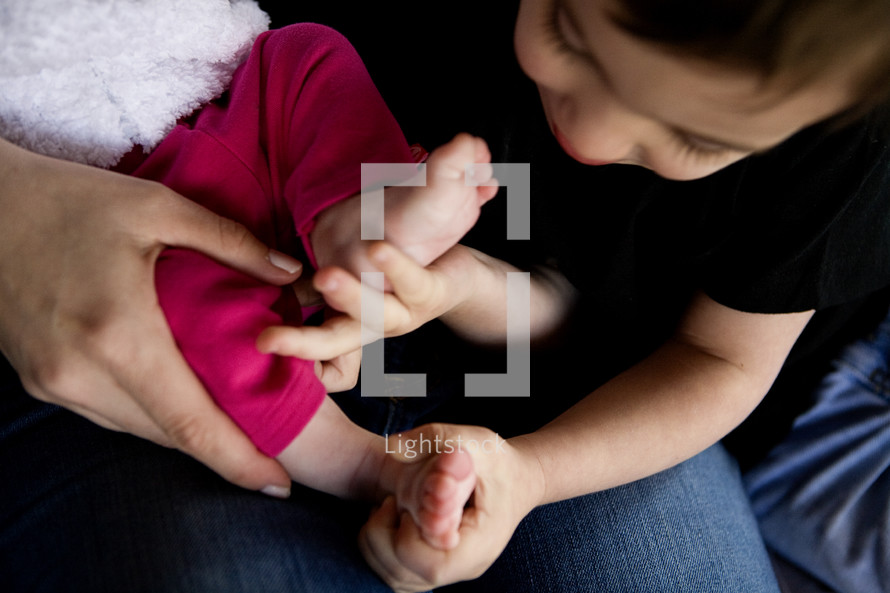 toddler brother holding his infant sisters feet