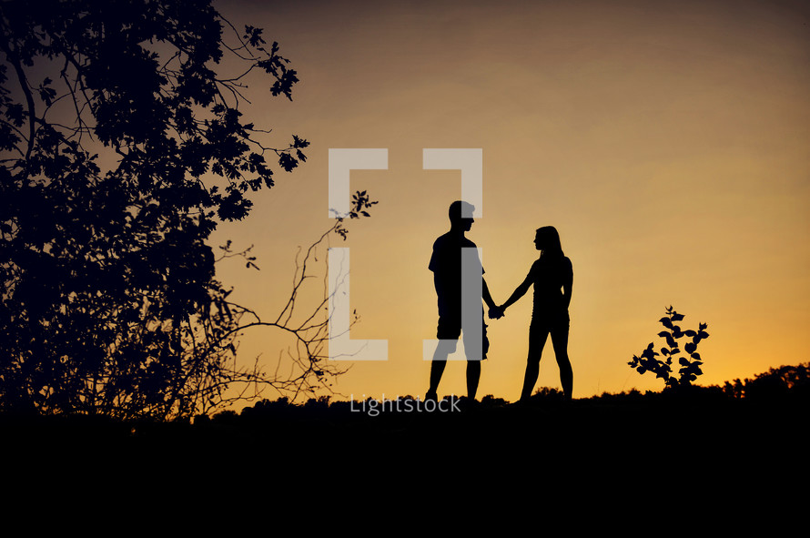 A silhouette of a couple holding hands.