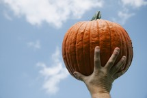 Man holding up pumpkin
