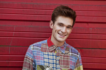 man in plaid standing in front of a red wall smiling
