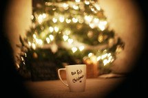 Christmas mug sitting in front of a tree