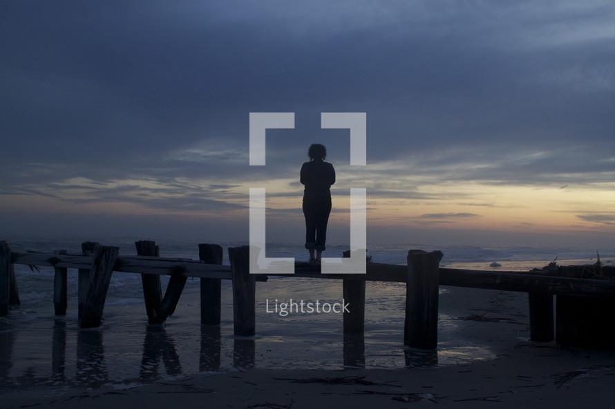 woman standing on the pillars of a broken pier