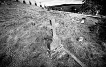 Cross headstone in hillside cemetary.