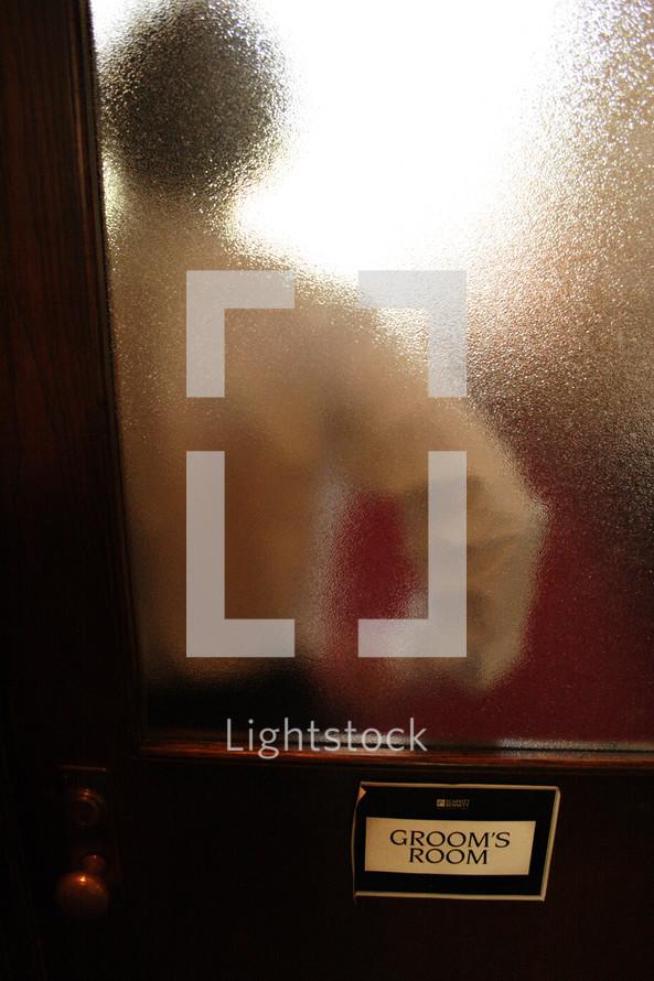 Groom standing behind a door