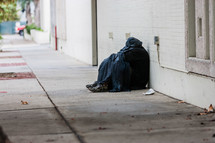 homeless man covered in a blanket on a sidewalk