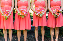 Bridesmaids in orange peach dresses with floral bouquets