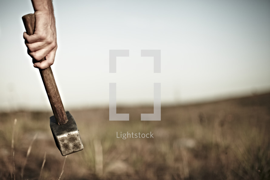 Man holding hammer in field