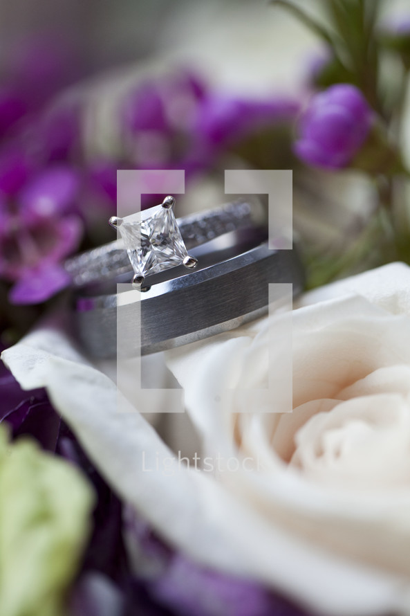 engagement ring and wedding band on bridal bouquet