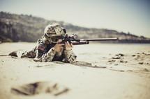 Military man shooting gun on a beach