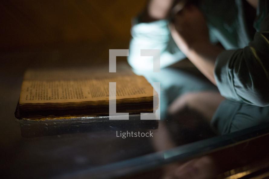 Man reading old worn BIble at desk