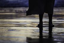 feet of Christ standing on wet sand