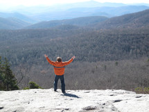 a man standing on a mountain top with raised hands