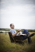 man reading a book in a leather chair sitting in a field