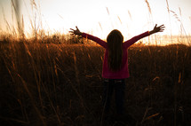woman in a field with her hands raised in worship to God