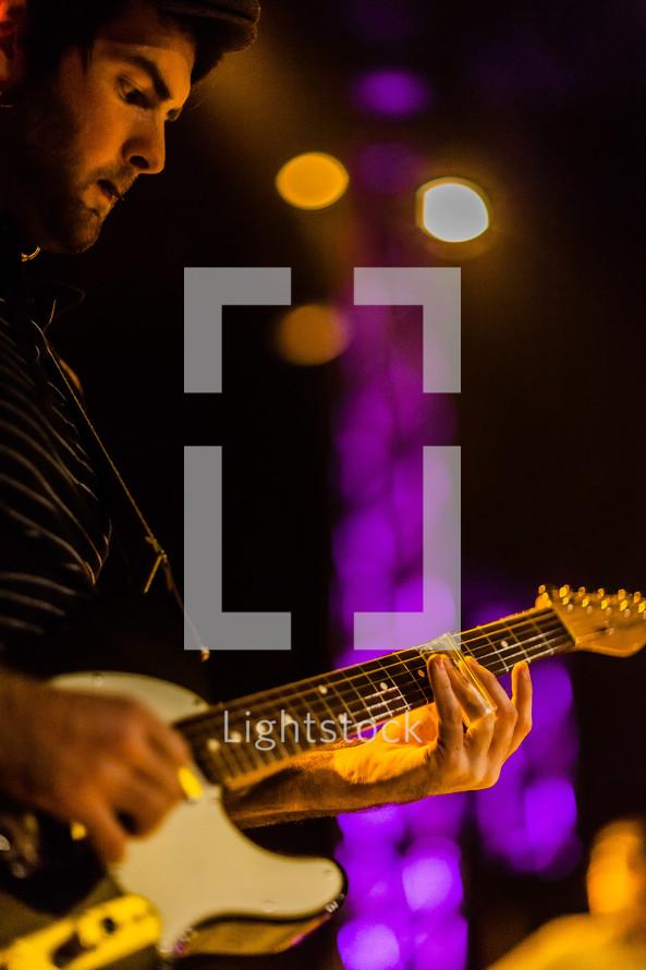 A man playing a electric guitar during worship