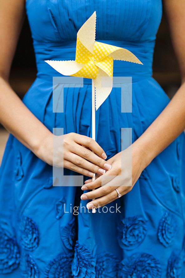 A woman in a blue dress holding a yellow whirligig pinwheel