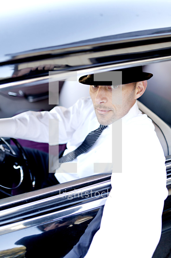man in a hat with his arm hanging out a car window fedora hat classic vintage 1940's gangster tie