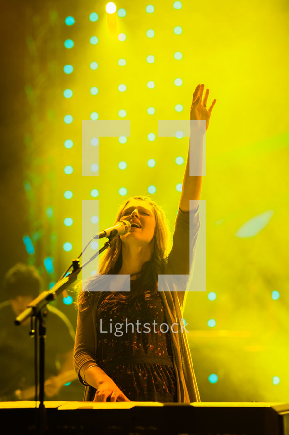 Woman with raised hand singing and playing keyboard worship leader praise