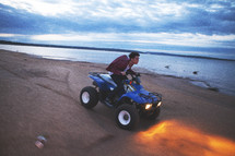 man driving a four wheeler on a beach