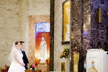 bride and groom praying at the altar