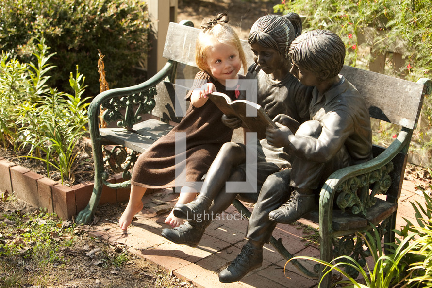 A young girl reading a book with statues on a bench