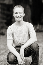teenage boy squatting and smiling in jeans and T-shirt portrait