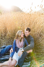 Happy Couple, man woman, sitting on blanket in field of gold tall wheat, embrace, love, romance, smile, engagement, marriage