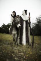 Mary riding on a donkey and Joseph