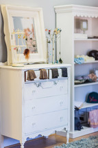 Girl's bedroom with white dresser, jewelry, socks, book shelf mirror