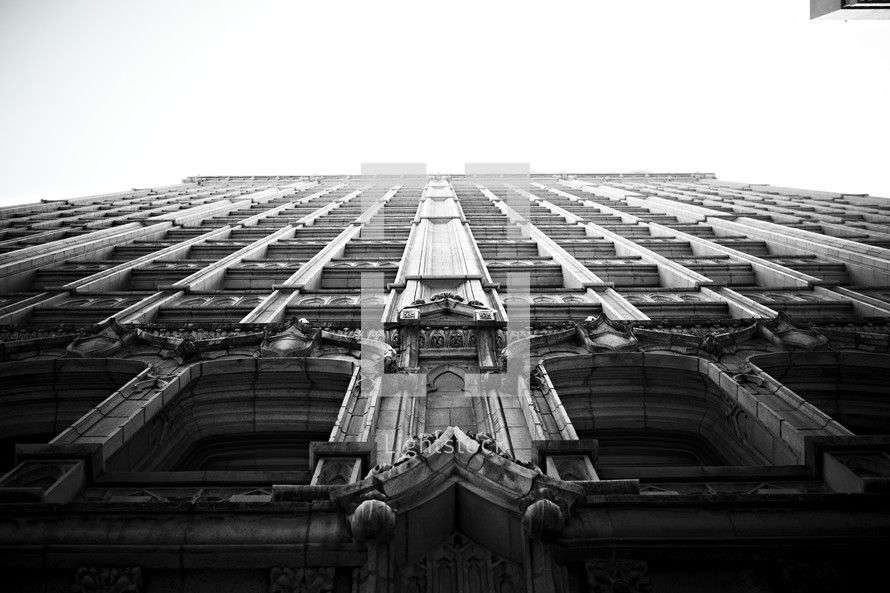 A tall building looms large over the sky.