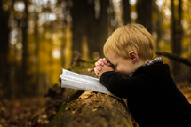 Boy outdoors praying over Bible