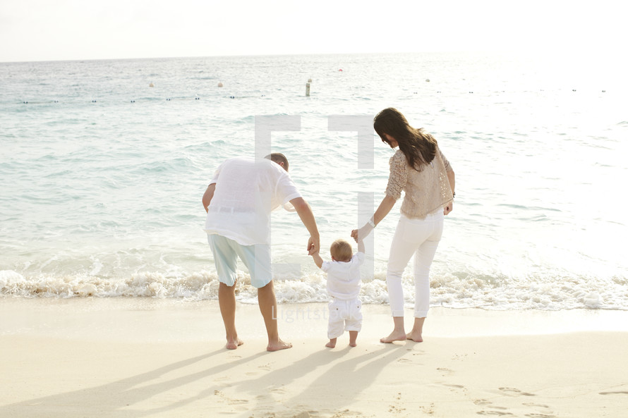 A young family stands on the beach at the edge of the ocean.