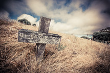 cross on a tombstone through tall grass