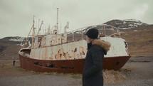 a woman walking next to a rusty ship