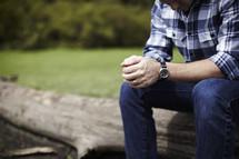 Man sitting on log praying