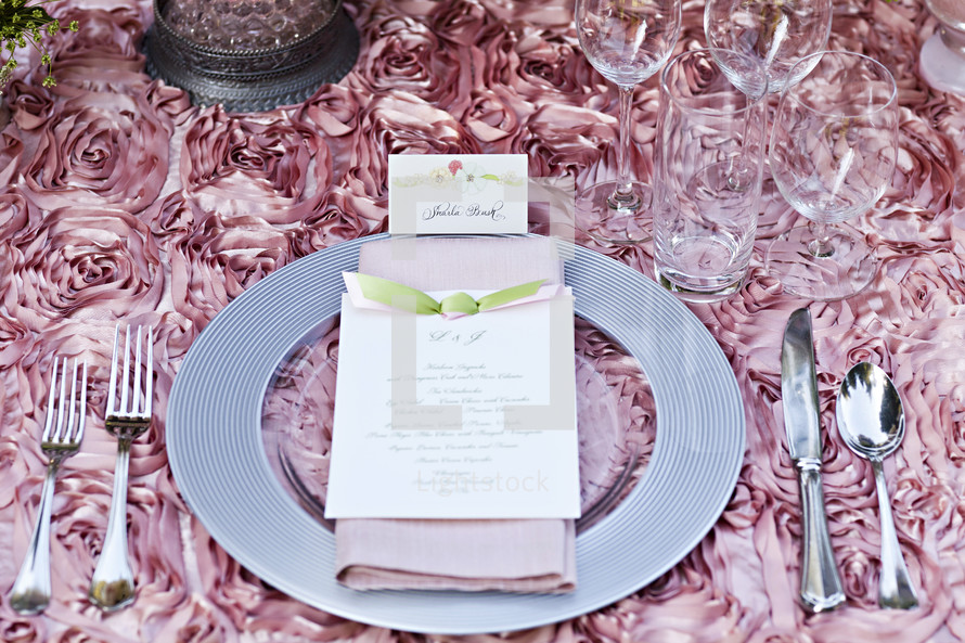 place setting with an invitation, pink table linen, flatware, wedding reception decor place card