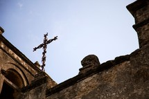 wrought iron cross on a stone building