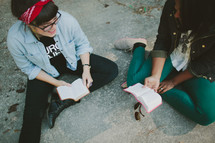 Friends sitting on ground reading Bible