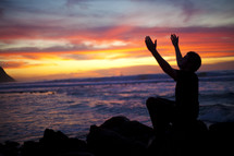 man sitting on a rock by the ocean with his arms raised in worship to God during a sunset