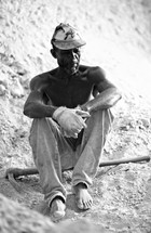 A black Haitian man sits after working hard